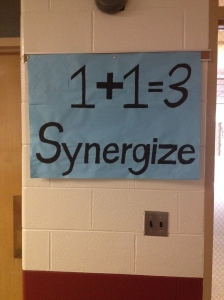 "Okay, I find it hard to believe kindergartener or first grader would understand this poster. Firstly, 1+1 =/= 3, so what if they start screwing up math because they think this poster is true? Also, SYNERGIZE. I don't think I knew what that word meant until middle school. I asked a teacher what this poster meant and she said it's an attitude training thing, like ""two people working together are greater than the sum of their parts. So, I see the logic there. But IDK about this poster…"